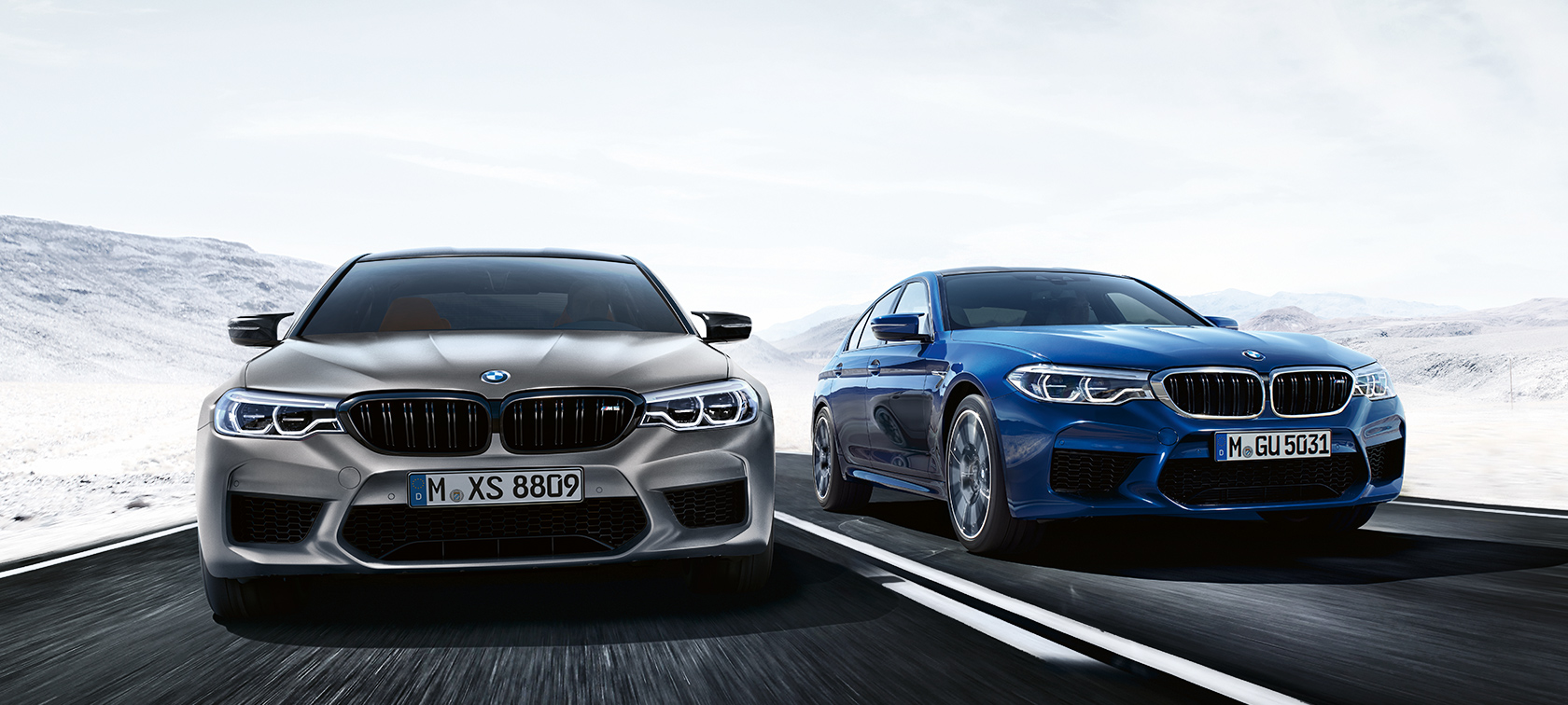 Grey M5 Competition and blue BMW M5 driving on highway in front of desert landscape