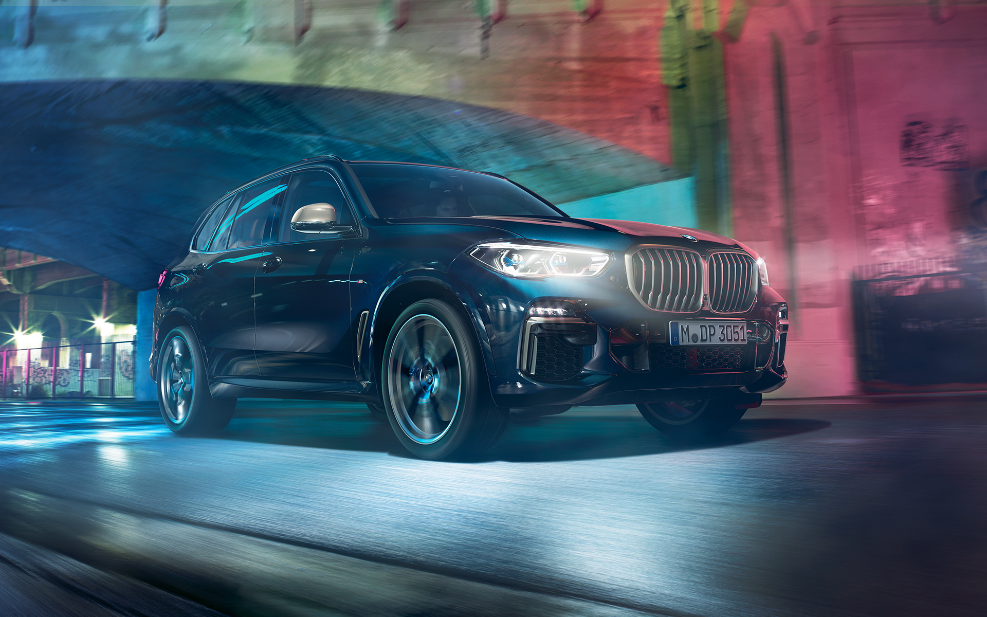 Driving shot of the BMW X5 M50d at night in an urban setting